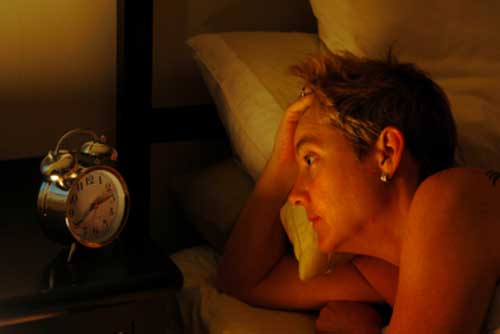 woman lying awake at night staring at her clock